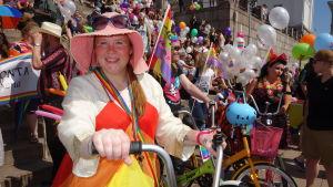 En person klädd i rengbågsklänning och  rosa solhatt med solglasögon på står på Senatstorget med en cykel. Regnbågsflaggor, människor och ballonger i bakgrunden