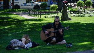 En man samlar in pengar genom att spela gitarr på en gräsmatta på sommaren.