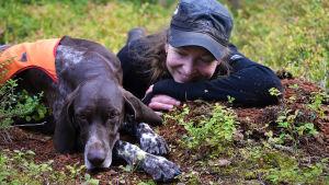 Nainen ja koira makaavat marjamättäällä.