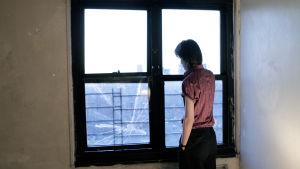 Yksi Angulon veljeksistä katselee kotona ulos ikkunasta. Kuva dokumenttielokuvasta The Wolfpack.