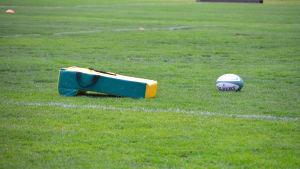 gul plastdyna och avlång rugbyboll på gräsplan.