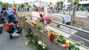 Människor lägger blommor vid ingången till tunnelbanestationen intill köpcentret Olympia på lördagen 23.7.2016