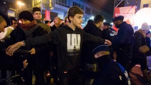 Polisen kroppsvisiterar en ung kille som ska gå in på festområdet i Bryssel.