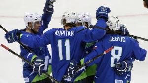 Blåklädda slovenska ishockeyspelare firar mål tillsammans.