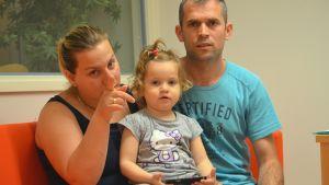 Mor, far och barn sitter på en soffa