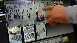 En tysk polis pekar på en skärm med övervakningsbild från torget i Köln.