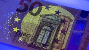 Framsidan av nya 50-eurosedeln belyses här med ultraviolett ljus.