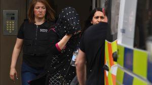 En kvinna förs ut ur ett bostadshus av polis i Barking.