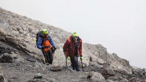 Aron Anderson och en till bergsklättrare, som går uppför ett berg. Aron har kryckor.