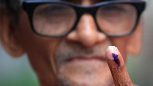 Indisk väljare visar sitt finger efter att ha röstat.
