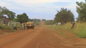 en bil levererar gin i gula plastdunkar i norra uganda