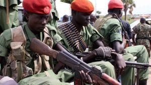 Sittande soldater i gröna uniformer, röda mössor och vapen.
