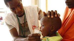 En läkare ger näringsberikad mat till ett undernärt barn i nordöstra Nigeria.
