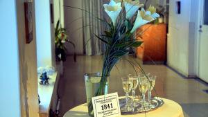Bord med blombukett och bricka med champagneglas.