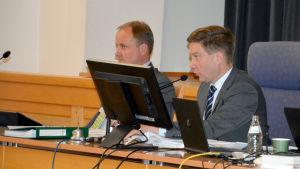 Ordförande Thomas Blomqvist vid Raseborgs stadsfullmäktiges presidium. I bakgrunden skymtar stadsdirektör Tom Simola.