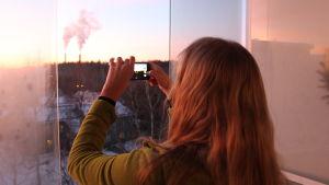 Nainen kuvaa parvekkeelta auringonlaskua kännykkäkameralla.