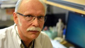 Porträttbild av Ingåläkaren Helge Heinonen i läkarrock och med stetoskop runt halsen.