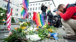 En man ber utanför USA:s ambassad i Berlin den 13 juni 2016. Regnbågsflaggor och USA:s flagga hänger vid ett stängsle och blommor och ljus ligger på marken.