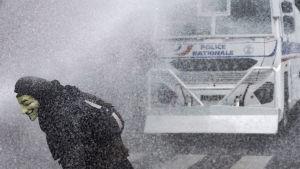 En maskerad demonstrant flyr polisens vattenkanon under demonstration i Paris 14.6.2016