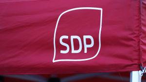 Socialdemokratiska partiets logotyp i vitt på en röd tältduk.