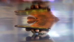En hand sticker ner en smarttelefon i vatten och en suddig eterisk spegling av handen och telefonen syns i ytan ovanför.