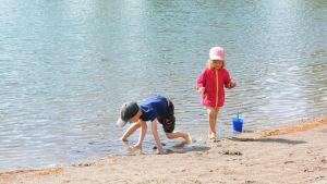 Barn leker på strand.