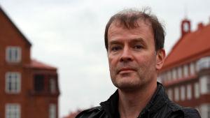 Författaren Mårten Westö med hus i bakgrunden