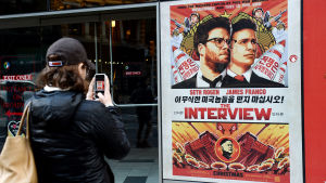 Kvinna fotograferar reklamaffisch för The Interview utanför Regal Theater i New York den 18 december 2014.