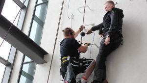 Pata Degerman håller mikrofonen då Ted Urho i direktsändning koncentrerar sig på ett trappsteg i taget.