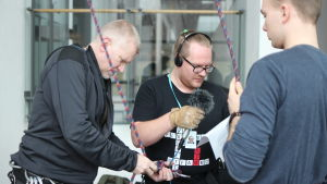 Pata Degerman sätter fast karbiner på Ted Urho som förbereder sig för intervjun. Matias Antoni assisterar.