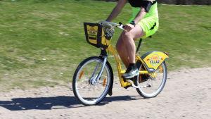 Man cyklar på citycykel i Helsingfors.