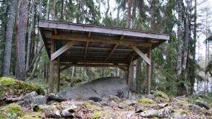 Egilrunstenen, under sitt tak i skogen.