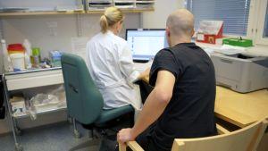 Patient och läkare på hälsocentral.