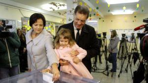 Litauens premiärminister, socialdemokraten Algirdas Butkevicius (till höger) med hustrun Janina och barnbarnet Kamilla i en vallokal i huvudstaden Vilnius 9.10.2016