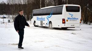 Fredrik Ström går framför en buss som körs av bolaget Wasabus. På en parkering. Vinter.