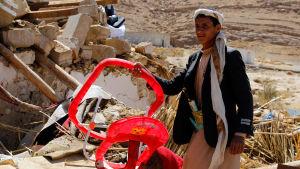 En yngling som överlevde attacken visar upp en barnstol från det totalförstörda, bombade huset