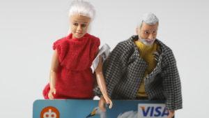Två dockor som ser ut som åldringar håller i ett bankkort.