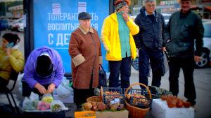 Ihmisiä myymässä sieniä ja omenoita kadulla Venäjällä