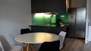 Ett köksbord med fyra stolar. I bakgrunden skymtar ett öppet kök.