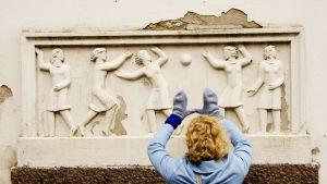 Minna Joenniemi ruotsinkielisen tyttökoulun reliefin vieressä