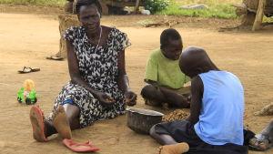en kvinna och två barn rensar jordnötter i norra Uganda