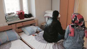 En man och en kvinna sitter på en säng.
