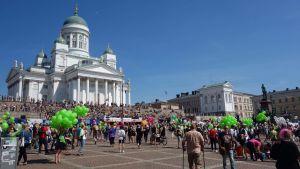 Senatstorget fylls med pridedeltagare och gröna ballonger under Helsingfors prideparad 2016.