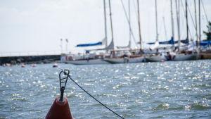En livboj i havet med segelbåtar som bakgrund.