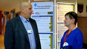 Göran Honga och Ann-Katrin Brandtberg står och diskuterar i aulan på Vasa centralsjukhus.