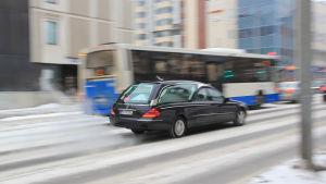 Likbil kör på gata i stad. Vinter.