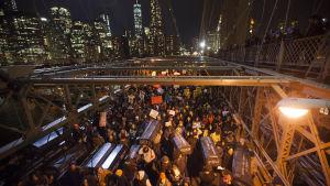 Demonstranter marscherar över Brooklyn Bridge i protest mot att en åtalsjury i New York beslutat att inget åtal kommer att väckas mot den polis som kvävde ihjäl den 43-årige Eric Garner sommaren 2014.