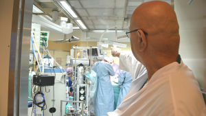 Hjärtkirurg Kalervo Werkkala står pekar in till en operationssal på Vasa centralsjukhus.