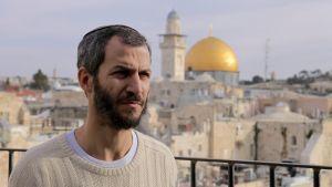 Juutalaisaktivisti Arnon Segal, taustalla vanha kalliomoskeija