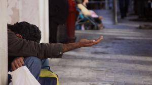 Mies kerjää rahaa käsi ojossa